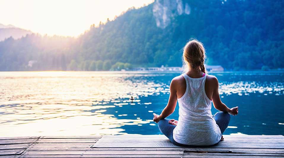 wanita sedang yoga di danau