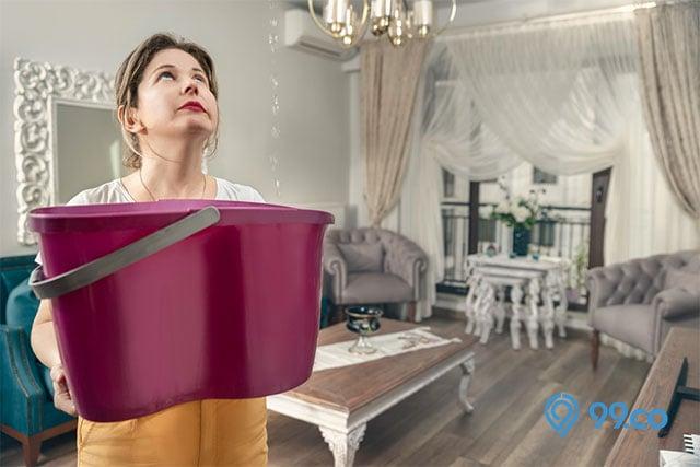 wanita pegang ember rumah bocor