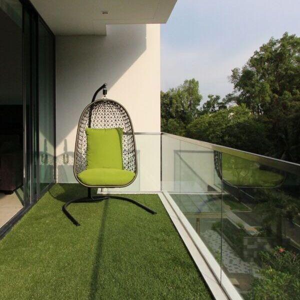 balkon kaca minimalis dengan rumput sintetis hijau