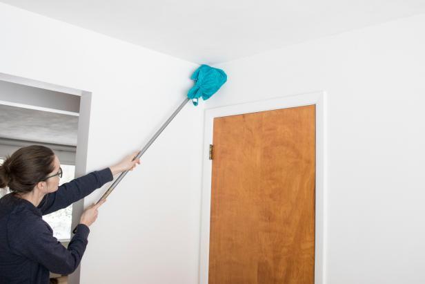 membersihkan debu dinding dengan sapu