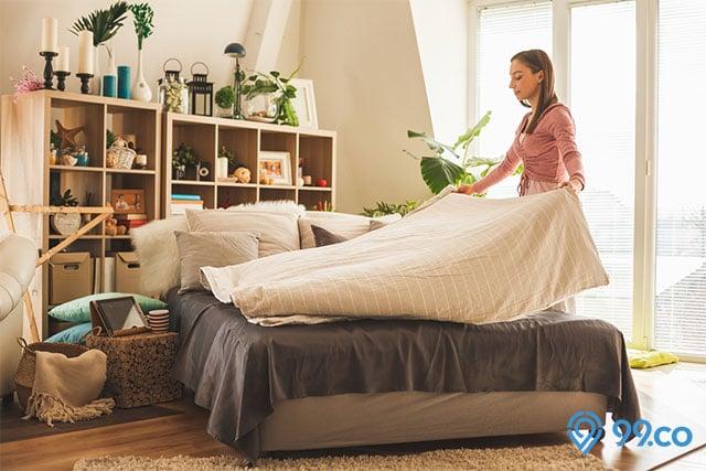 membereskan tempat tidur