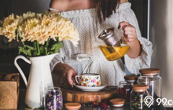 menuang teh ke dalam gelas