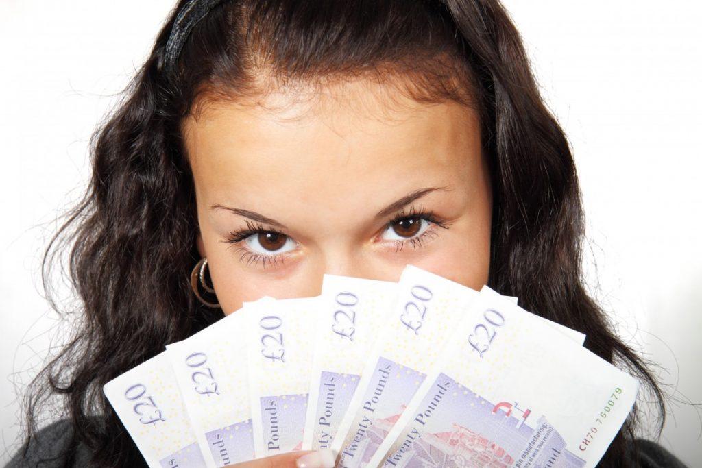 wanita memegang uang kertas