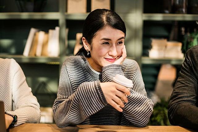 perempuan tersenyum minum kopi